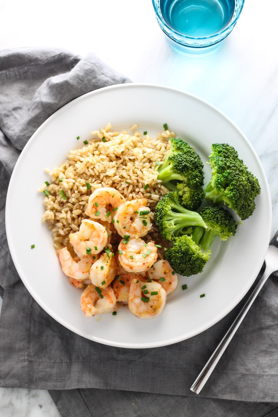 A plate with maple-dijon shrimp, steamed broccoli, and brown rice.