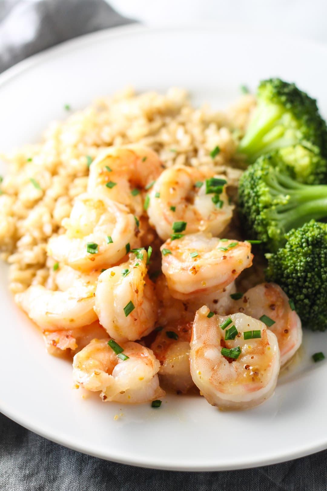 A close up of low FODMAP maple dijon shrimp topped with snipped chives.
