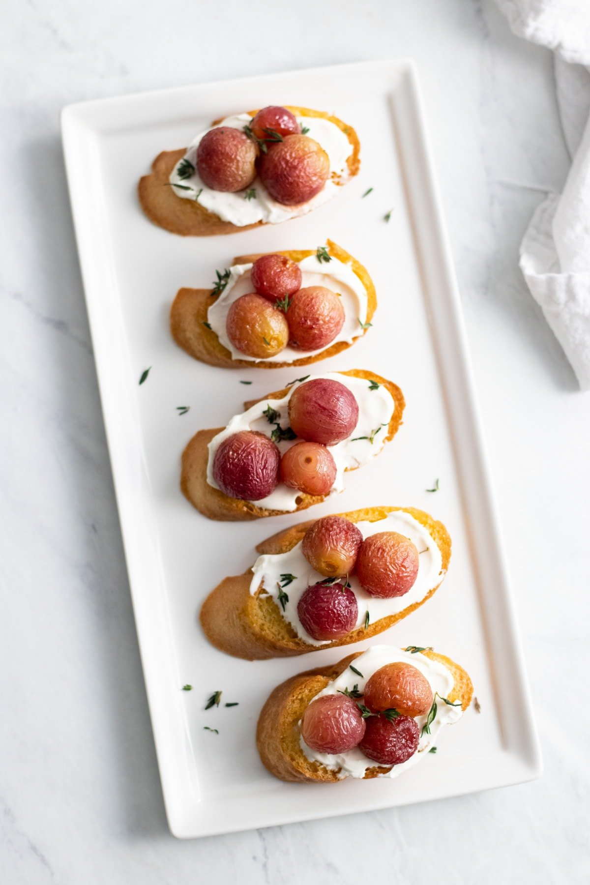 A rectangular platter with five toasted baguette slices topped with cream cheese, roasted grapes, and fresh thyme leaves.