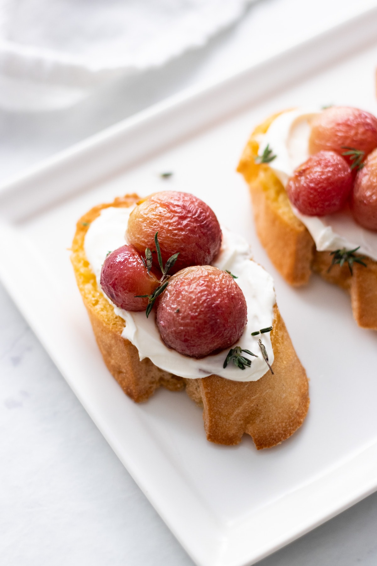 A crostini spread with lactose-free cream cheese and topped with roasted grapes and fresh thyme.