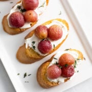 toasted baguette slices topped with lactose-free cream cheese, roasted grapes and fresh thyme leaves