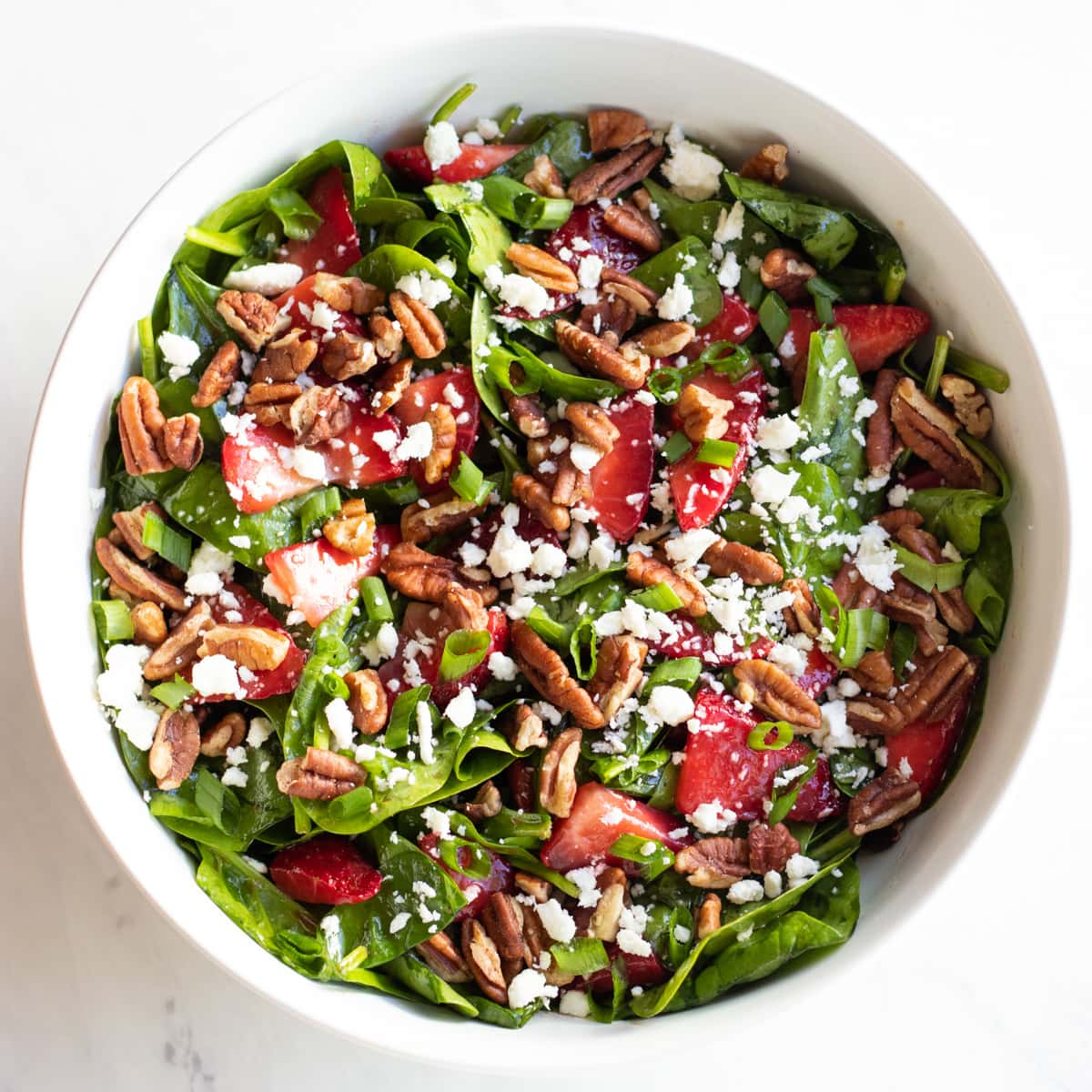 A large white bowl filled with spinach, sliced strawberries, pecans, crumbled feta cheese, and sliced green onion tops.
