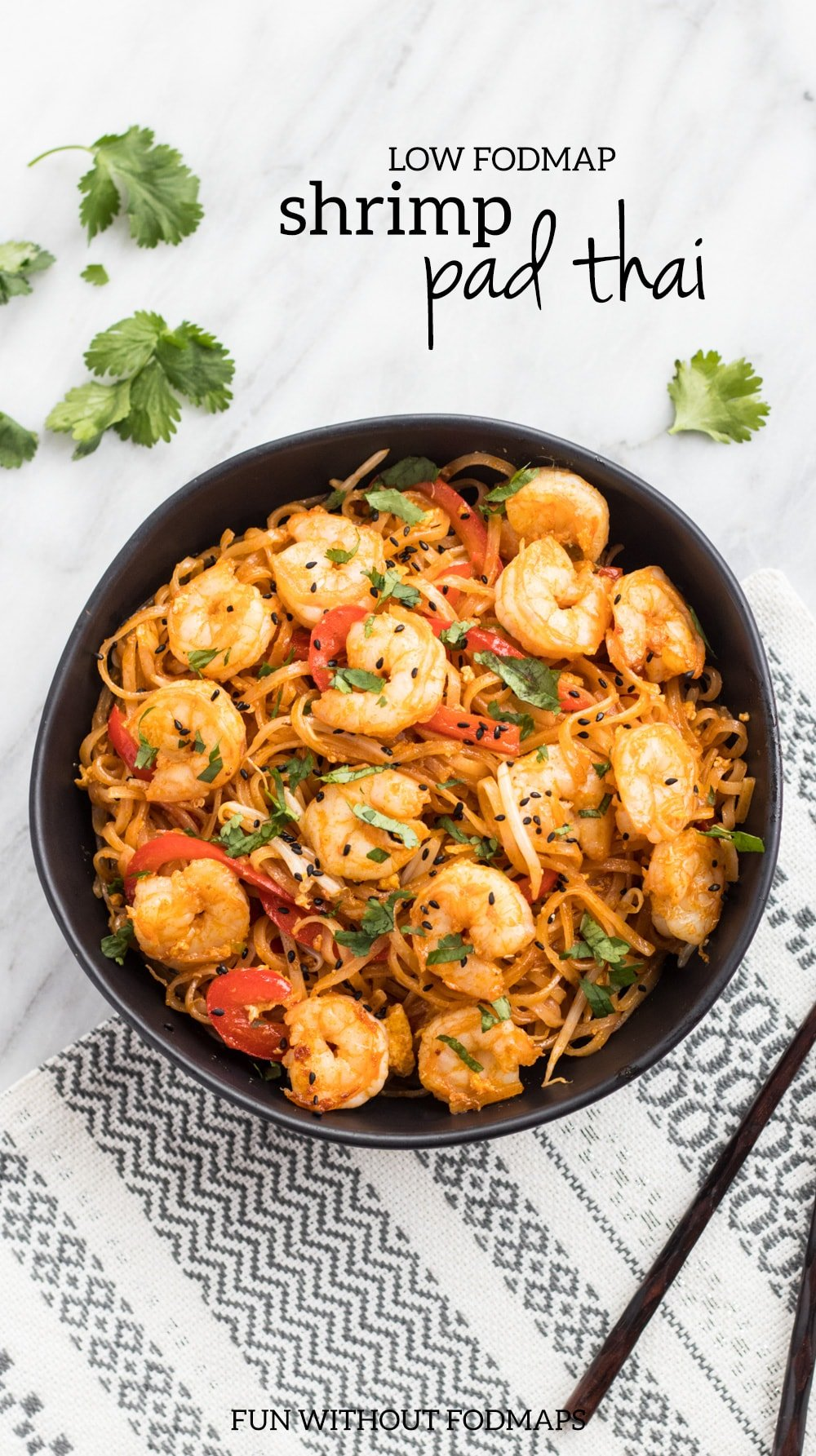 """Low FODMAP shrimp pad thai in a black bowl on a white marble background. Black text reads """"low FODMAP shrimp pad thai"""" in the upper right corner."""