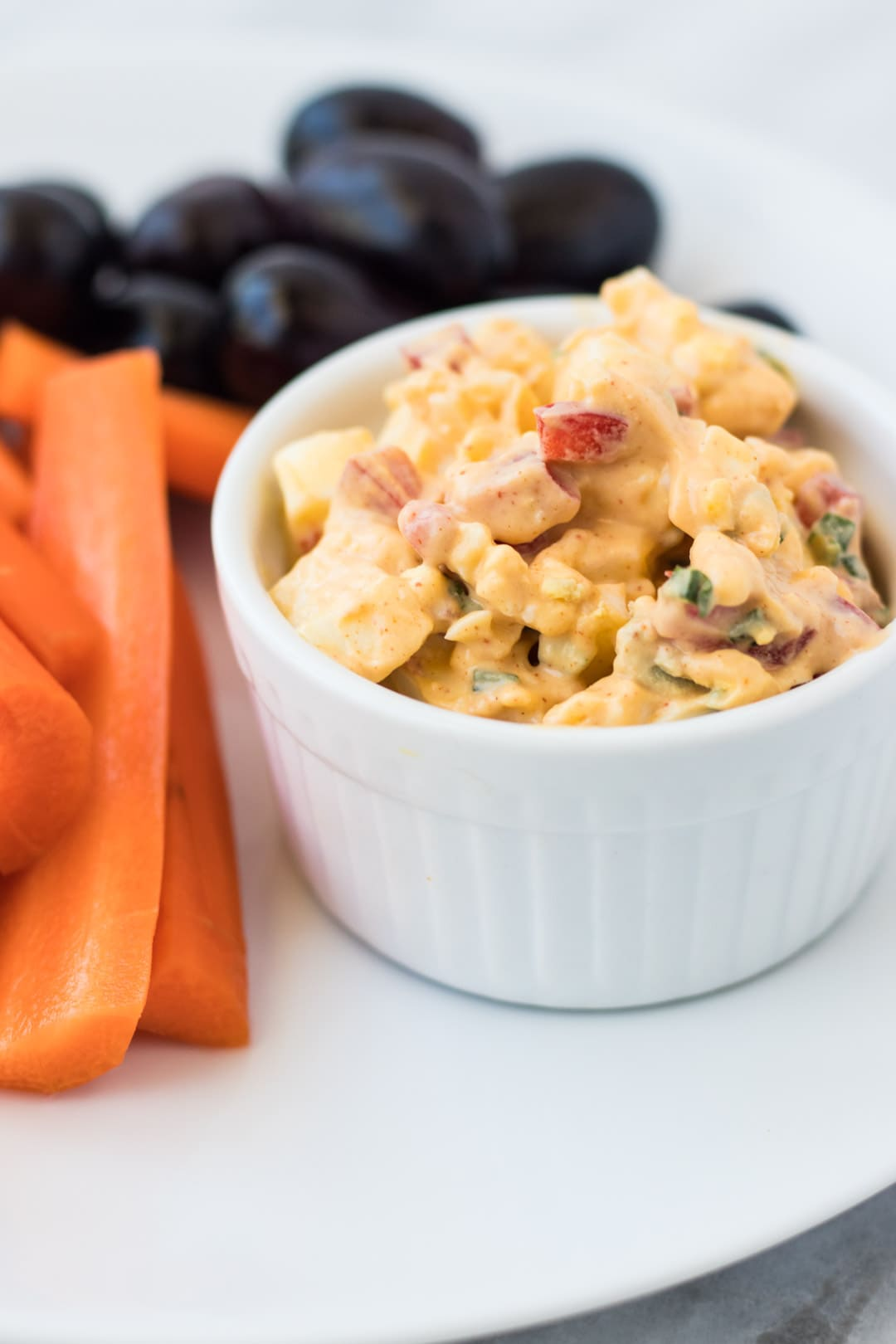 Dish of low FODMAP egg salad with carrot sticks and olives