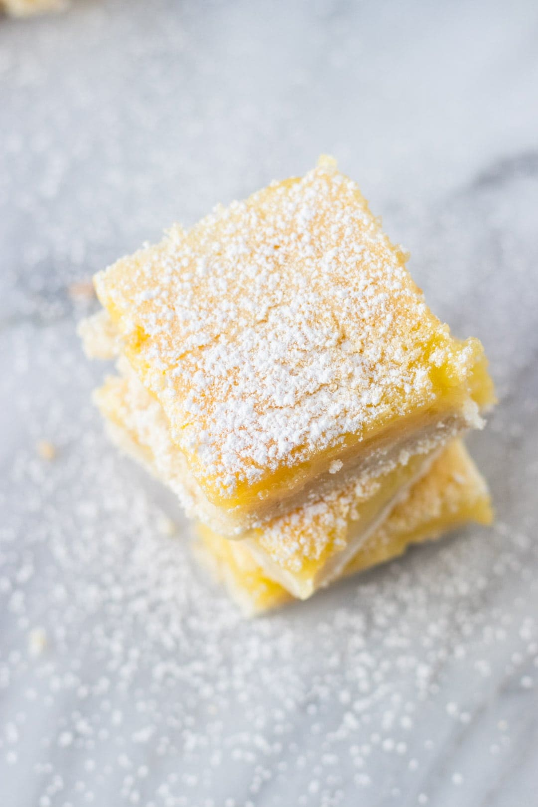 Stack of low FODMAP lemon bars dusted with powdered sugar.