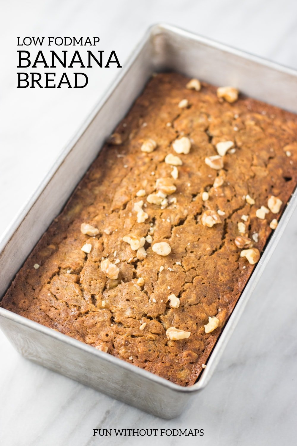 """A loaf pan filled with low FODMAP banana bread sitting on a white marble slab. Black text reads """"low FODMAP banana bread"""" at the top left and """"FUN WITHOUT FODMAPS"""" centered at the bottom."""