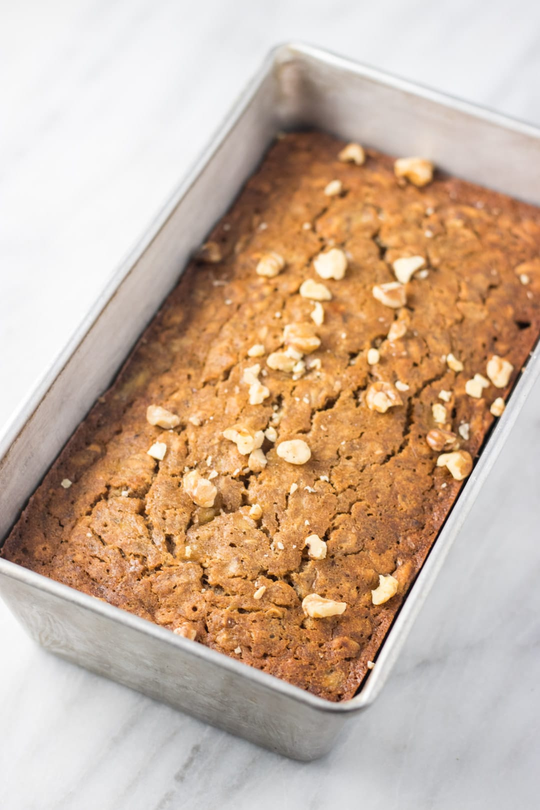 A loaf of low FODMAP banana bread dotted with walnut pieces.