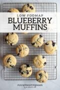 "A batch of blueberry muffins on a cooling rack. A black text overlay reads ""Low FODMAP Blueberry Muffins."""