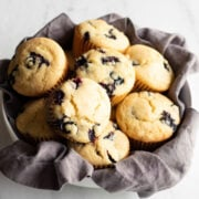gluten-free blueberry muffins in a bowl lined with a cloth napkin