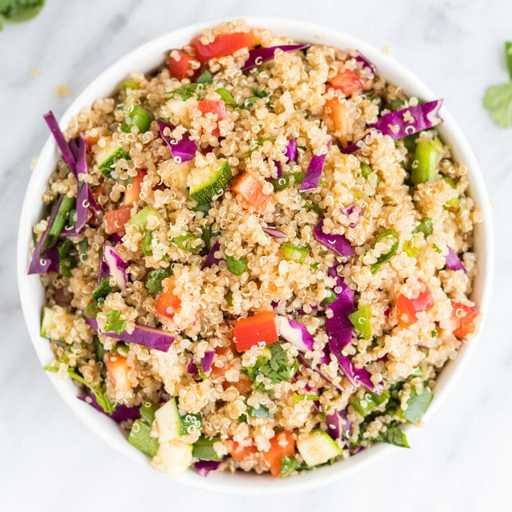 A bowl of a quinoa salad studded with colorful veggies.