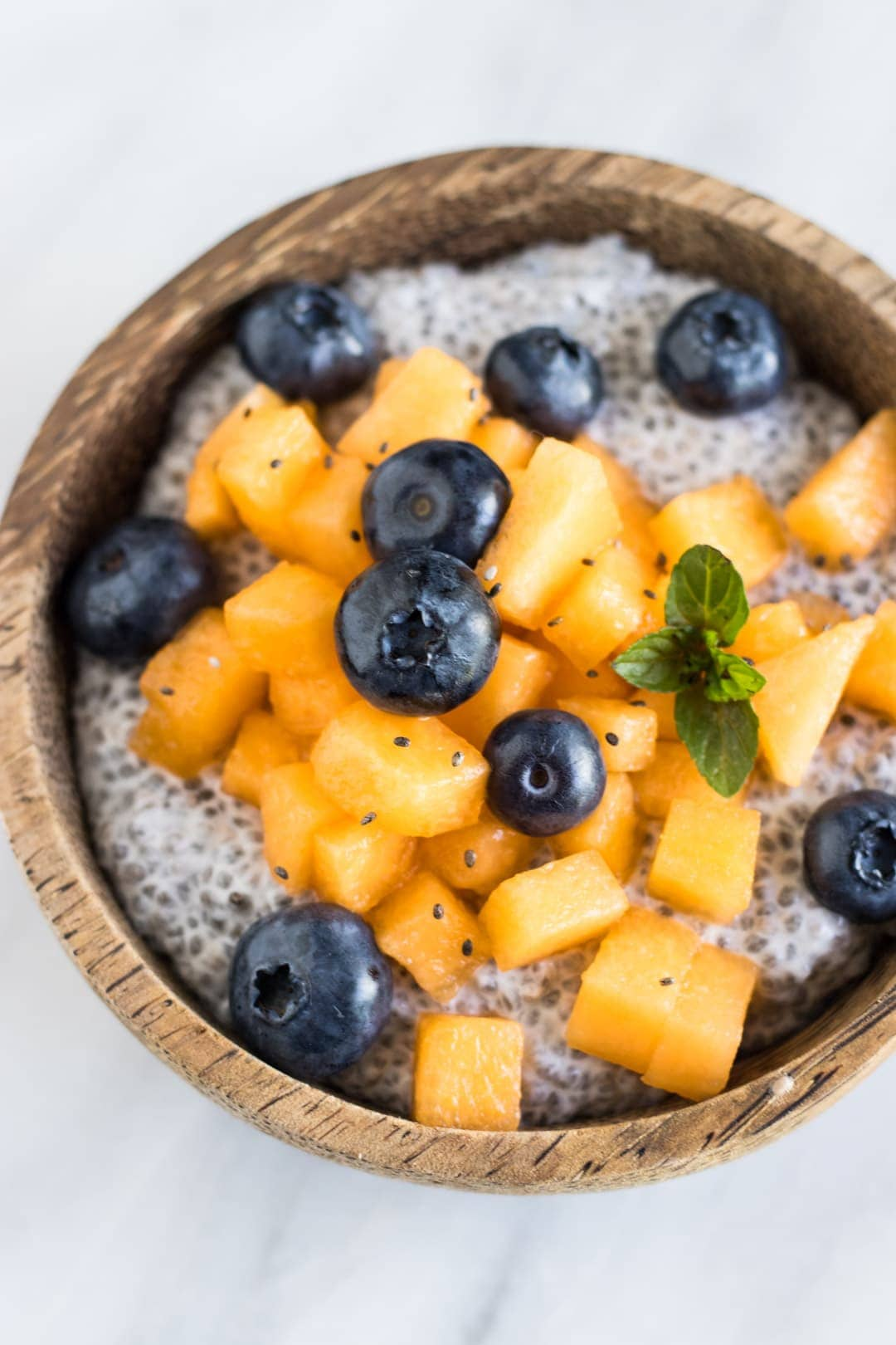 A bowl of chia pudding topped with diced cantaloupe, blueberries, and small mint leaves.