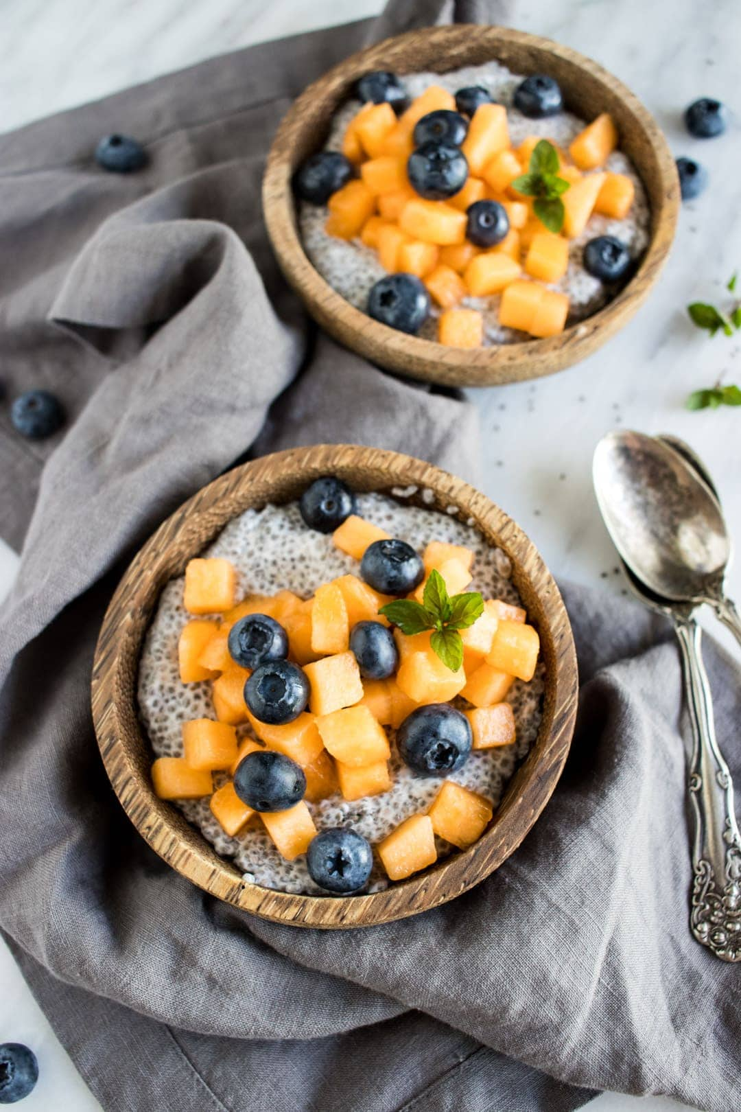 Two bowls of coconut chia pudding topped with blueberries and cantaloupe