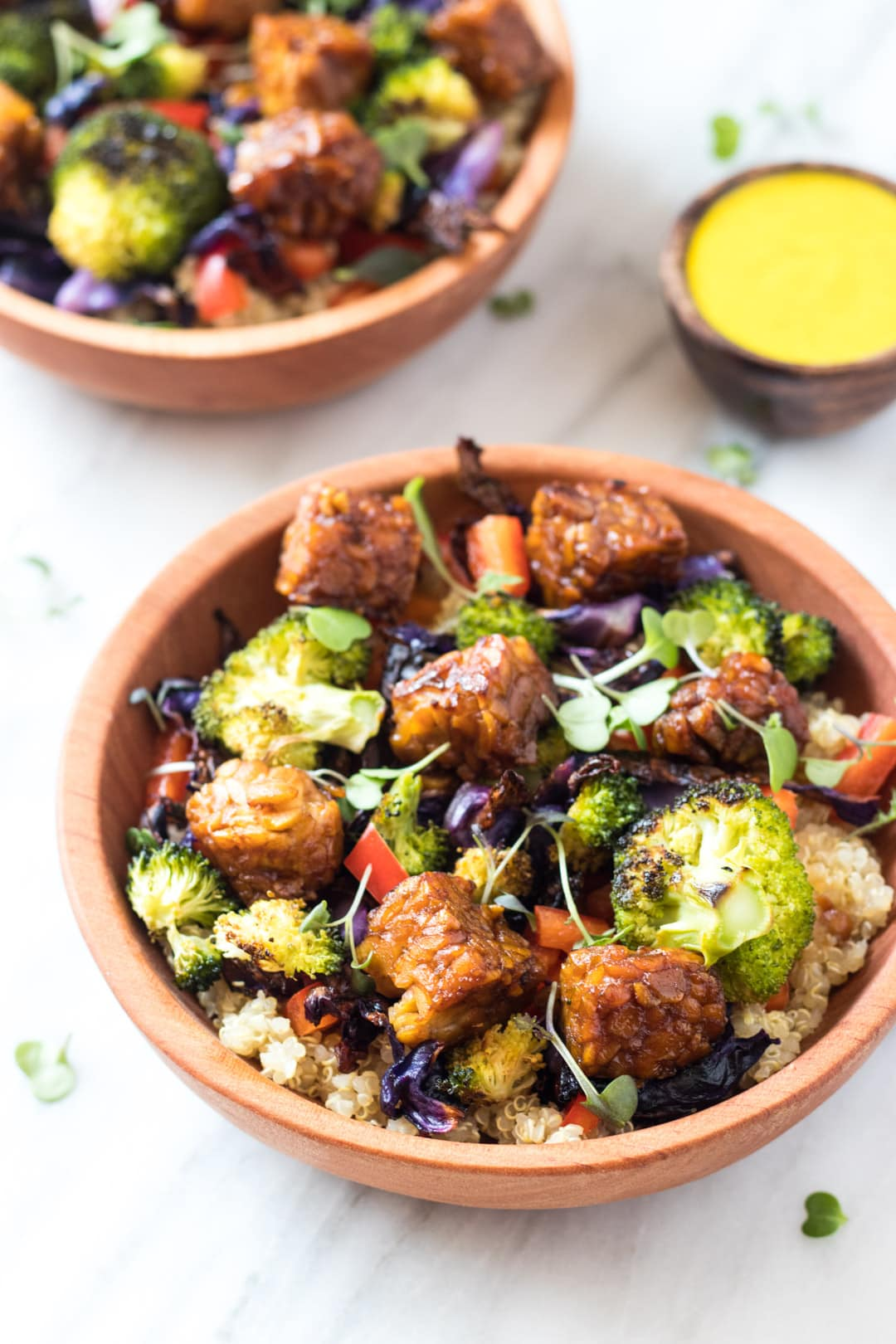 Two wooden bowls filled with low FODMAP rainbow bliss bowls or quinoa with roasted broccoli, cabbage, red pepper, and optional tempeh. There is also a small wooden dish filled with turmeric-tahini dressing.