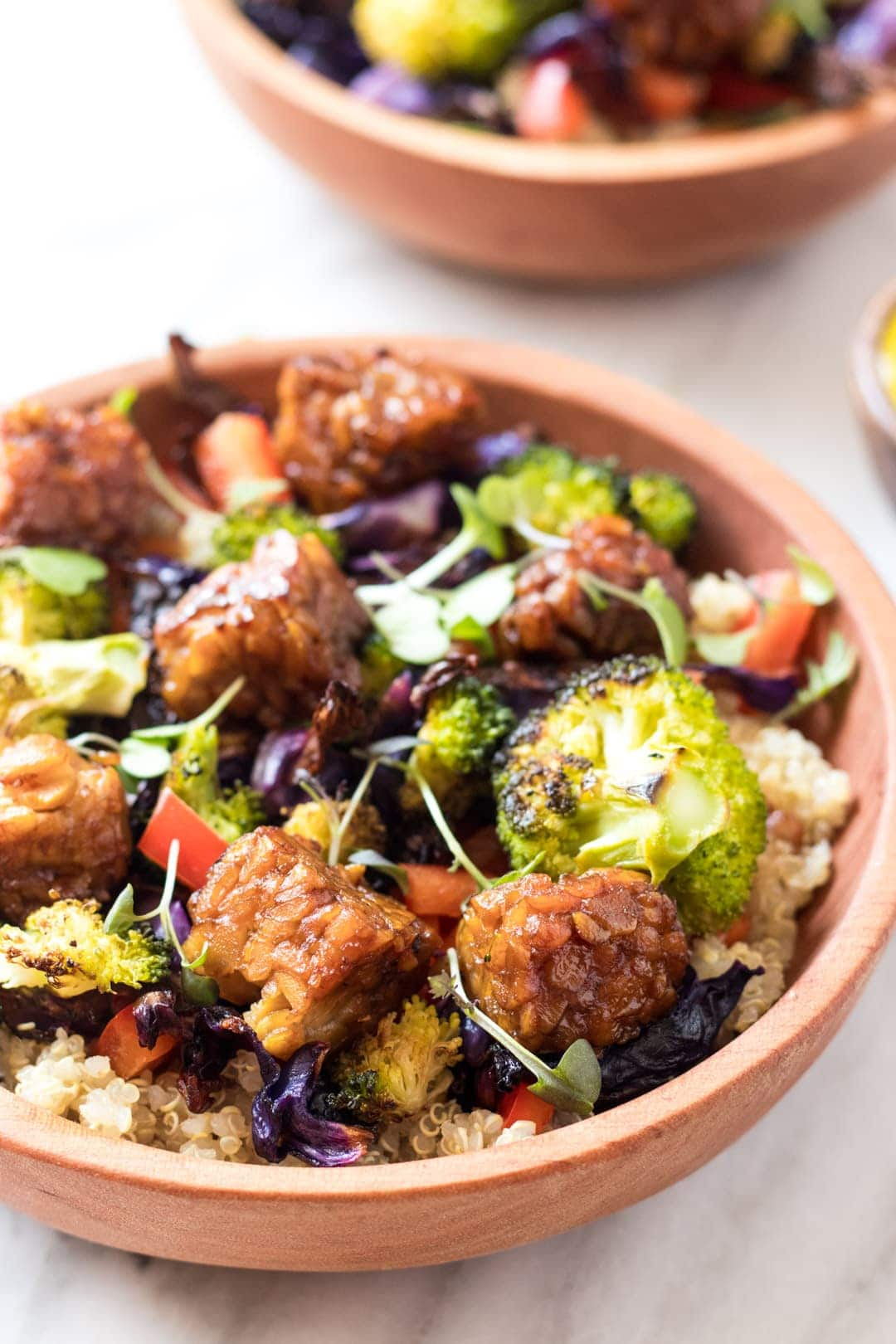 A close up low FODMAP rainbow bliss bowls filled with quinoa, roasted broccoli, red cabbage and red pepper (in low FODMAP servings). They're also topped with optional tempeh.