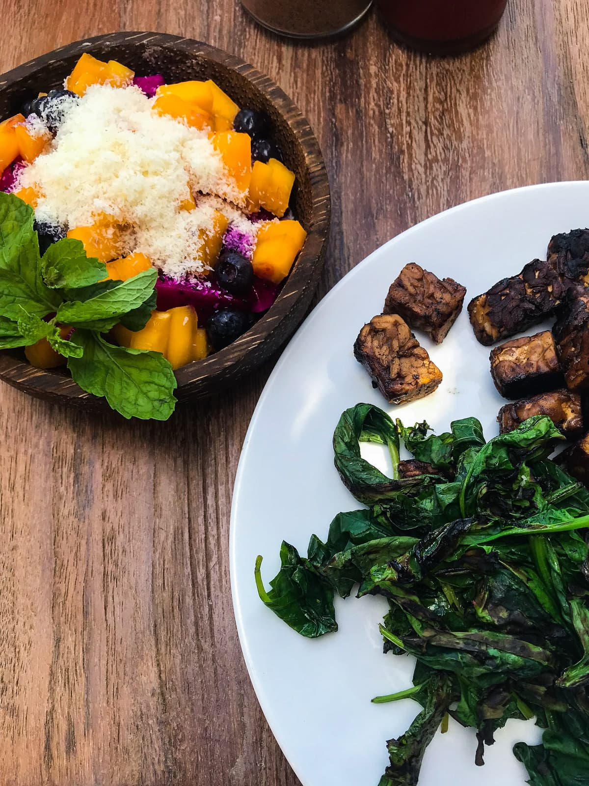 A plate of tempeh and sauteed greens with a bowl of tropical fruit on the side.