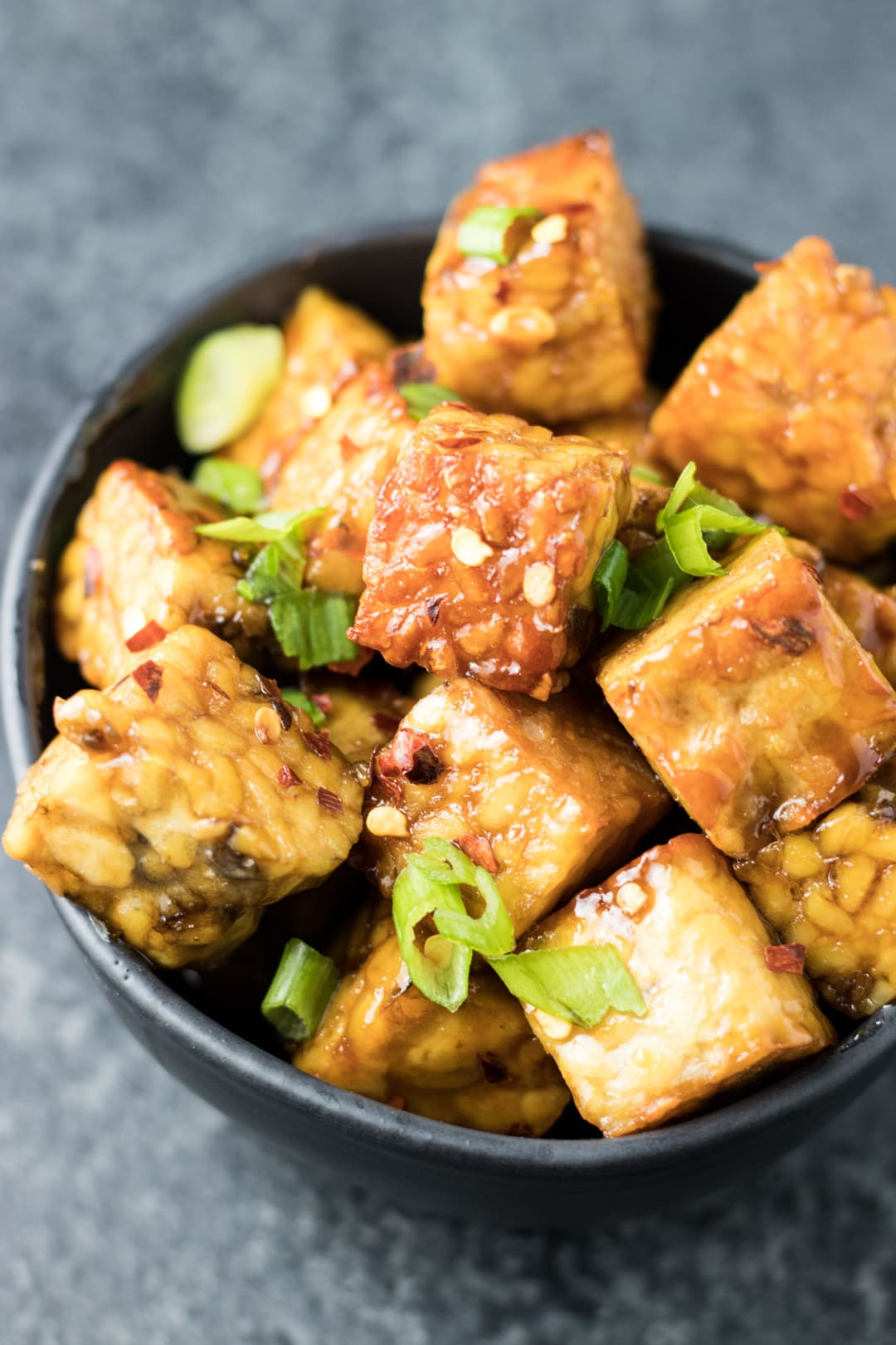 Browned tempeh tossed in a maple-soy glaze and topped with sliced green onions and red pepper flakes.