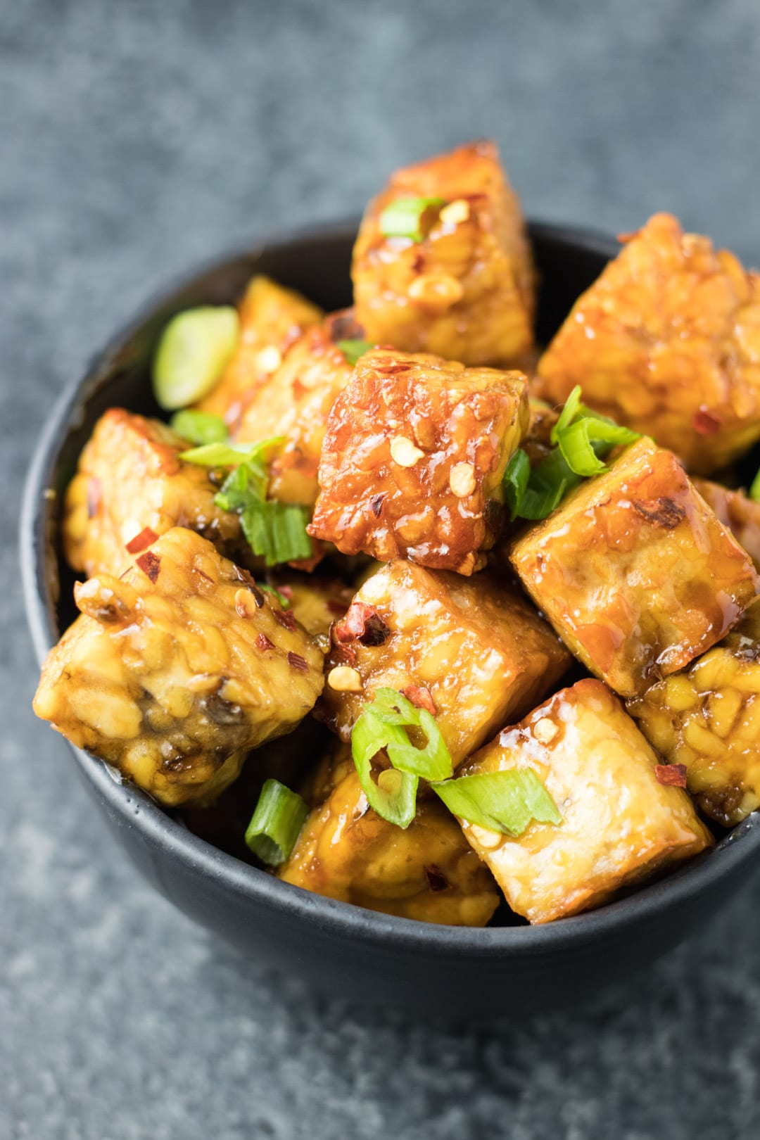 A bowl of seared tempeh cubes tossed in a maple-soy glaze and topped with sliced green onions