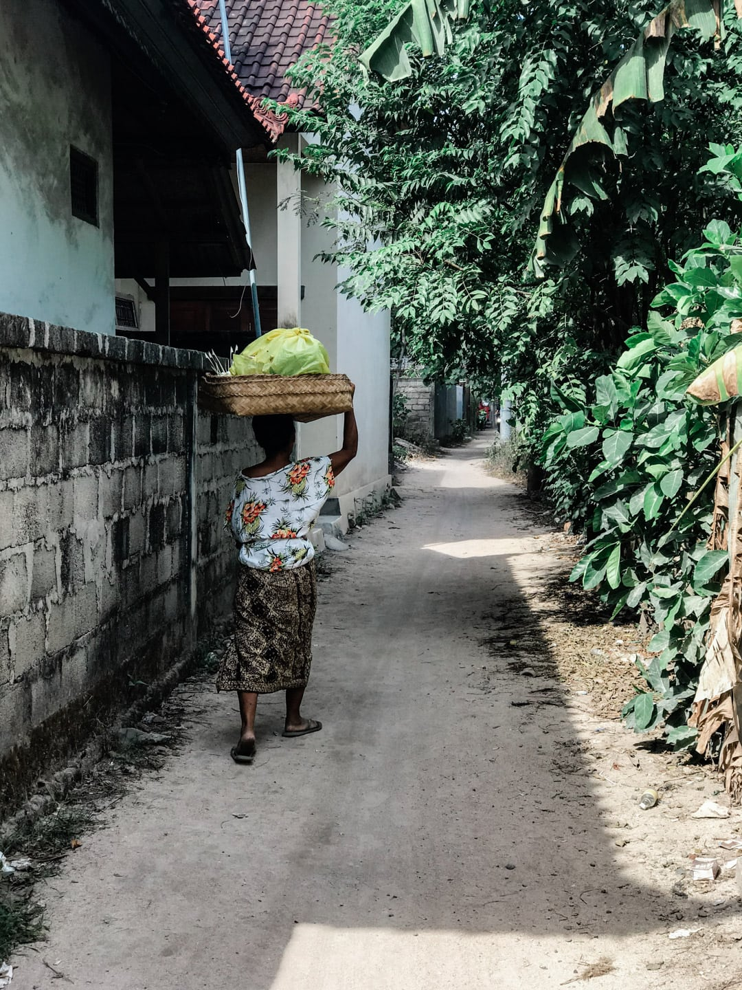 A local Lembongan woman carries a basket her head as she walks down an alley.