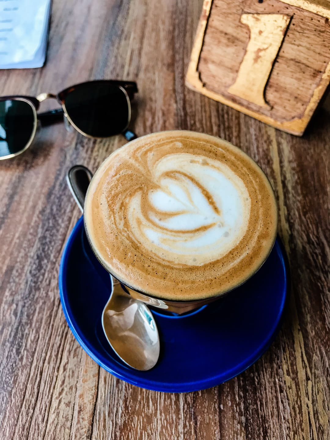 A small coconut milk latte with a small spoon on a blue plate. Rayban sunglasses and a wooden table marker with number one on it in the background.