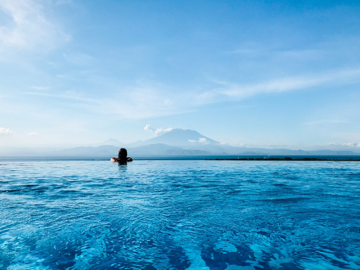 Woman swimming in an infinity pool overlooking the ocean with a volcano in the distance.