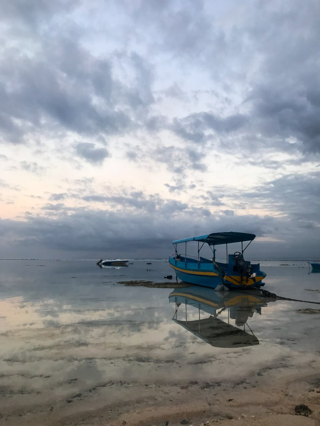 Still water reflects the sky and boat in Lembongan