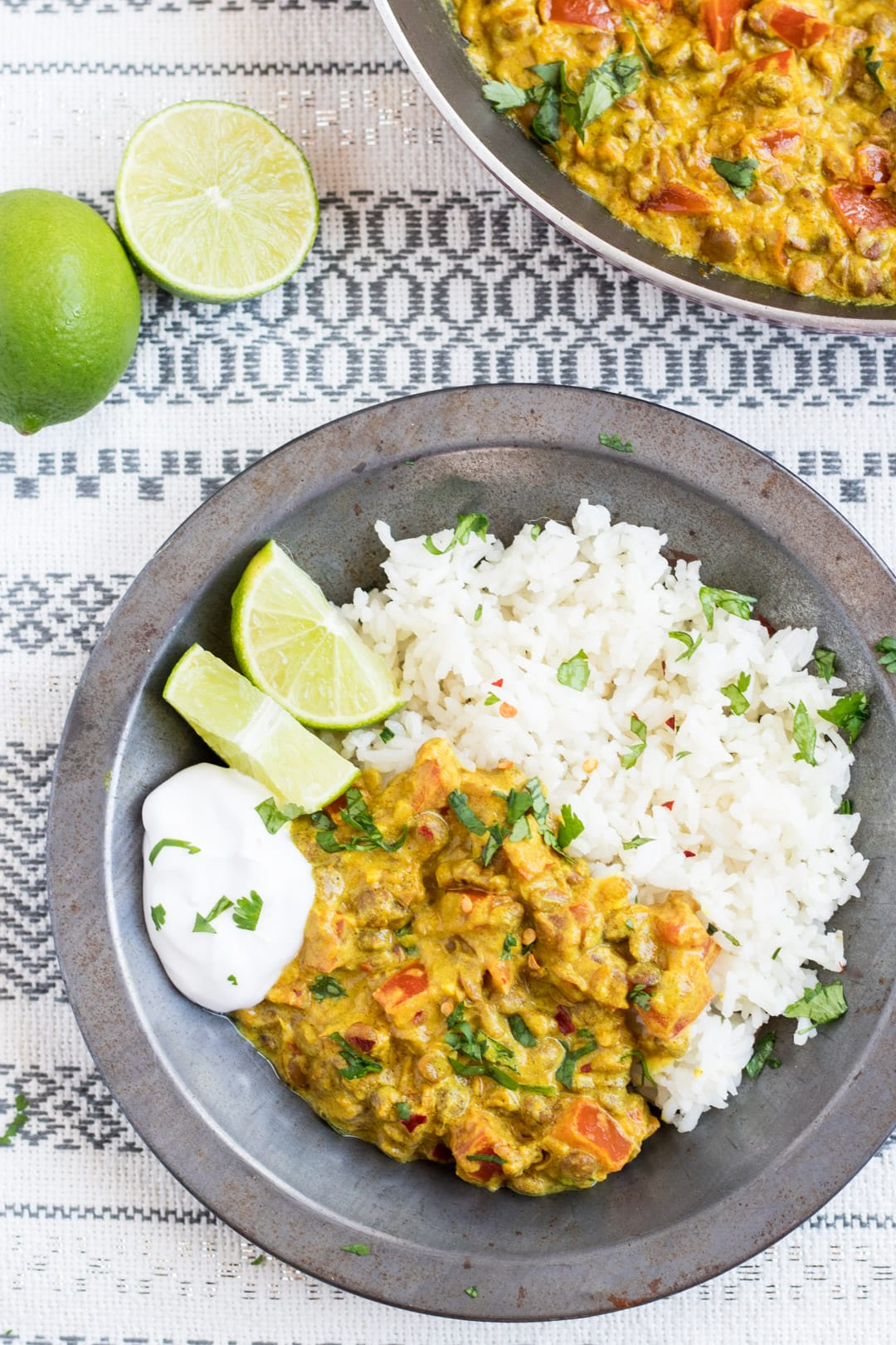 A metal bowl filled with low FODMAP lentil dal and basmati rice garnished with cilantro and served with lime wedges and a dollop of coconut yogurt. Limes and a skillet filled with dal in the background.