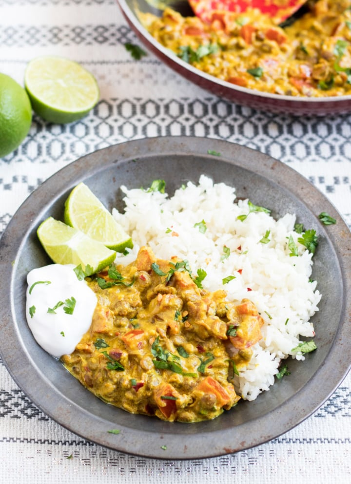 A metal bowl filled with low FODMAP lentil dal and basmati rice garnished with cilantro and served with lime wedges and a dollop of coconut yogurt.