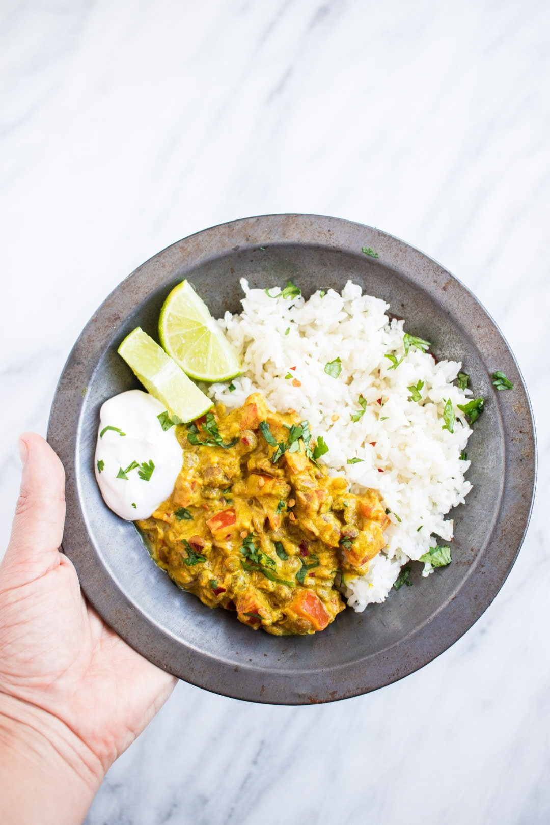 A hand holding a metal bowl filled with low FODMAP lentil dal and basmati rice garnished with cilantro and served with lime wedges and a dollop of coconut yogurt.