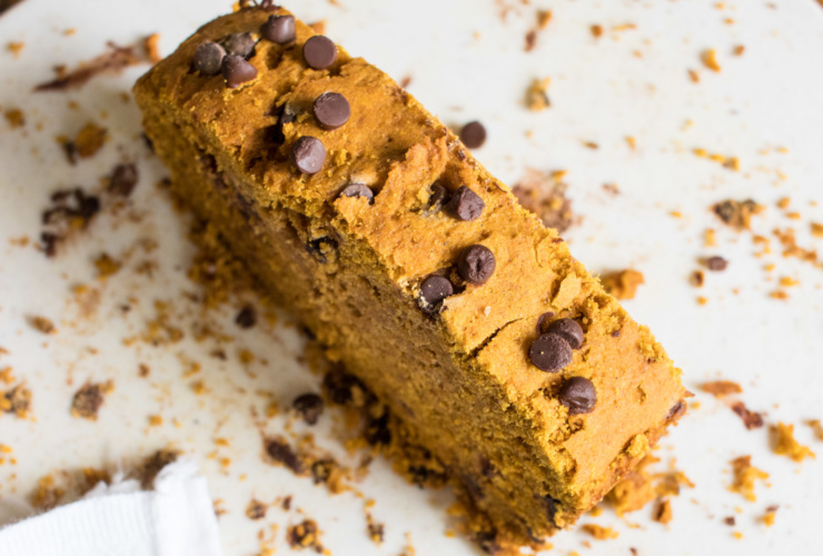 A thick slice of low FODMAP pumpkin bread dotted with chocolate chips on a white cutting board surrounded by crumbs.