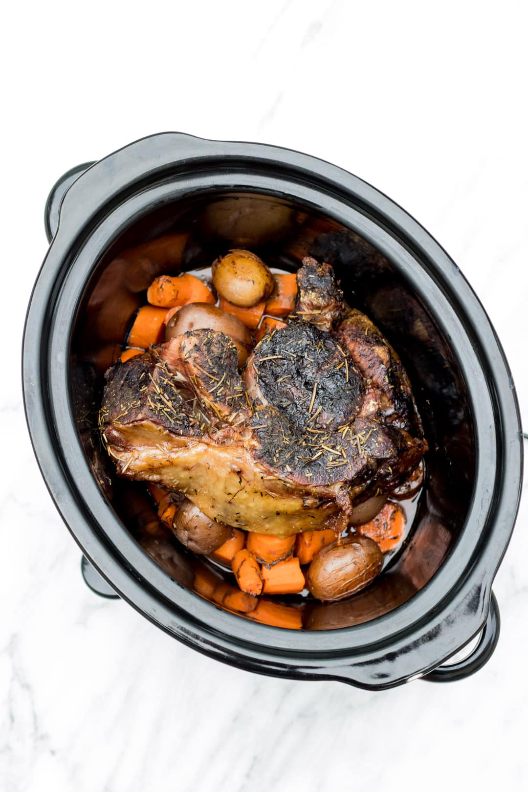 A crockpot filled with potatoes, carrots, and beef roast.