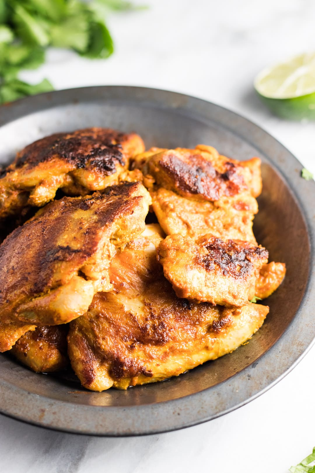 A close up of grilled tandoori-inspired chicken in a metal bowl.