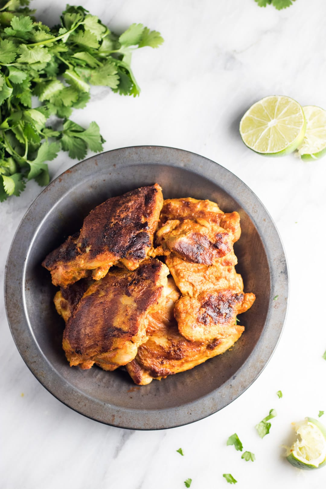 Grilled low FODMAP tandoori-inspired chicken in a metal bowl sitting on a white marble background. Cilantro leaves and lime slices surround the bowl.