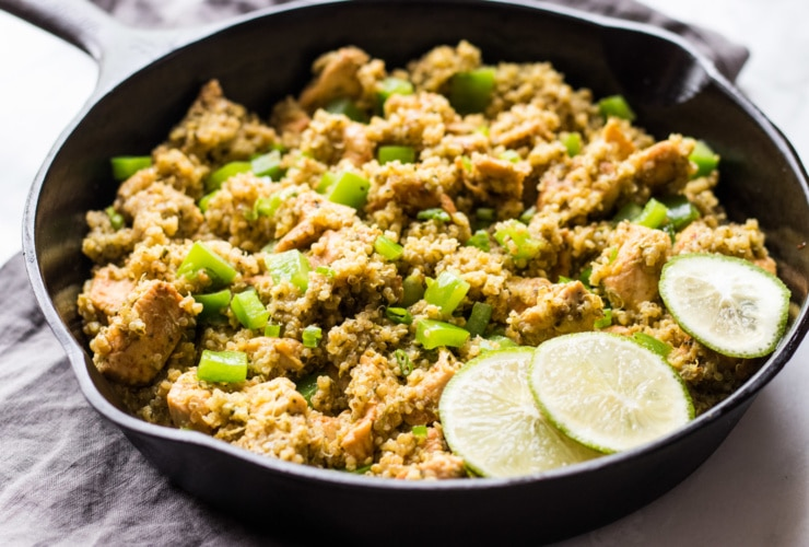 Cast iron skillet filled with low FODMAP cilantro lime quinoa with chicken, diced green bell peppers and a garnish of three lime slices.