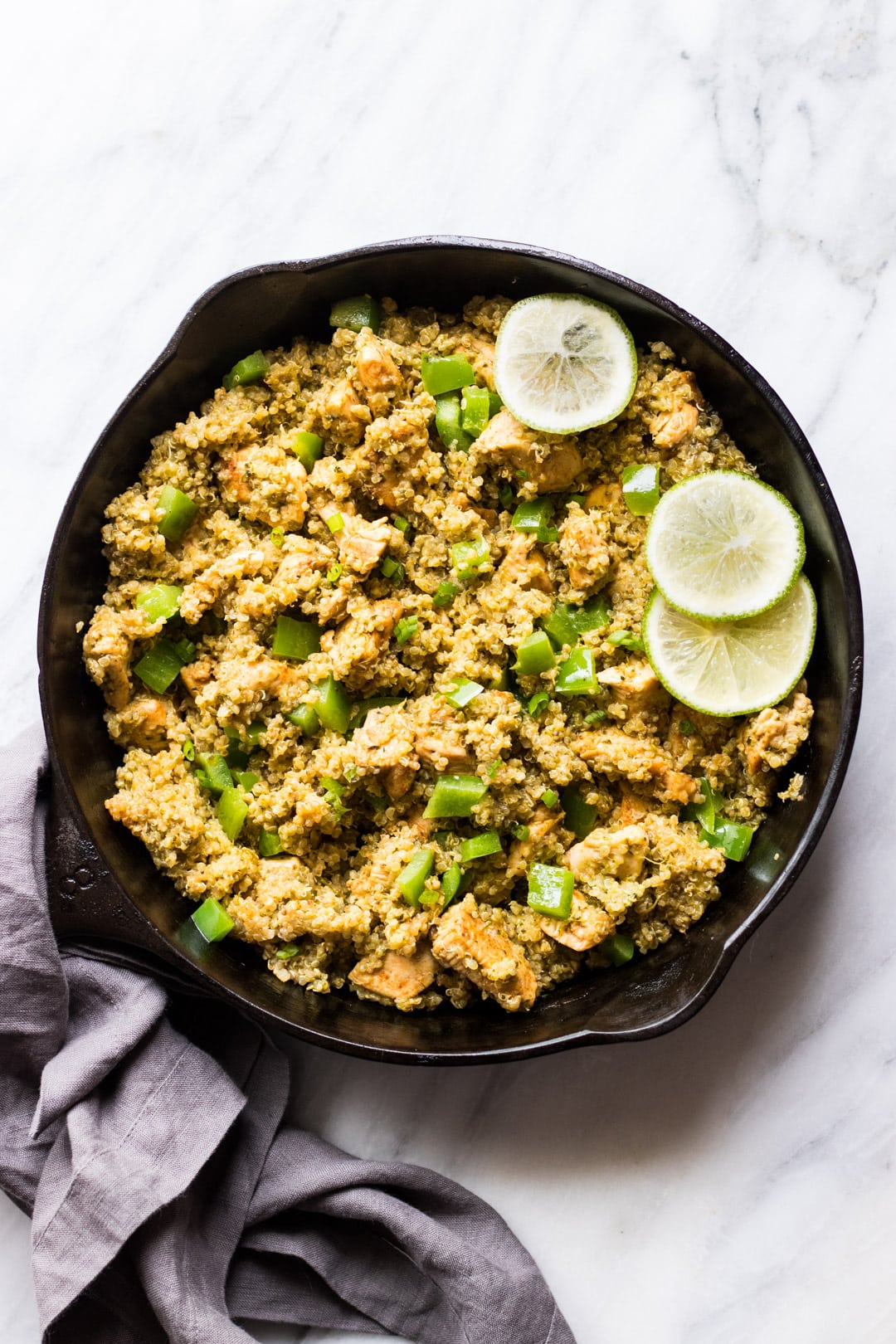 Low FODMAP cilantro lime quinoa with chicken in a cast-iron skillet on a marble slab with a blue-gray cloth napkin wrapped around the skillet handle.