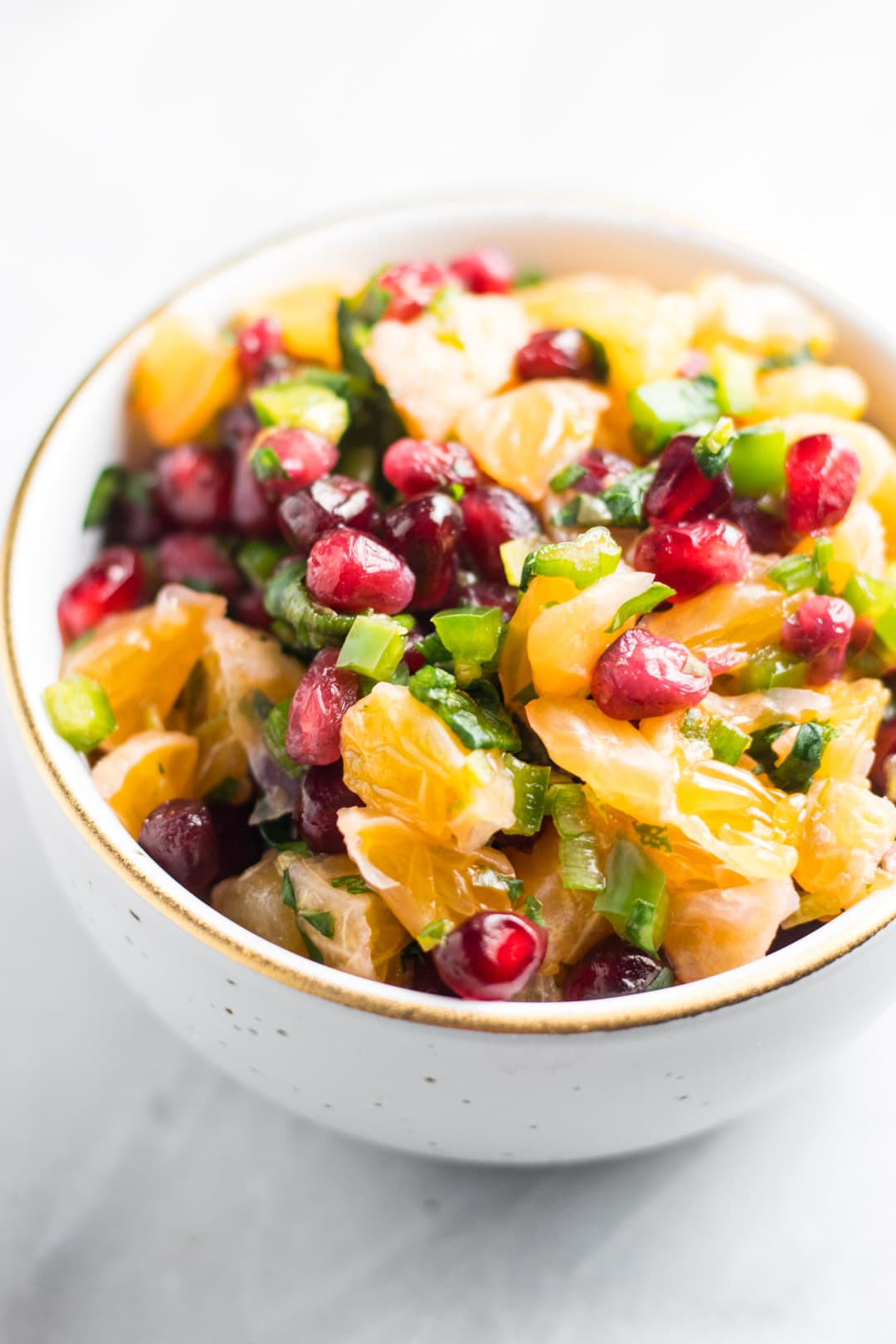 Low FODMAP Pomegranate Orange Salsa in a gold-rimmed white bowl.