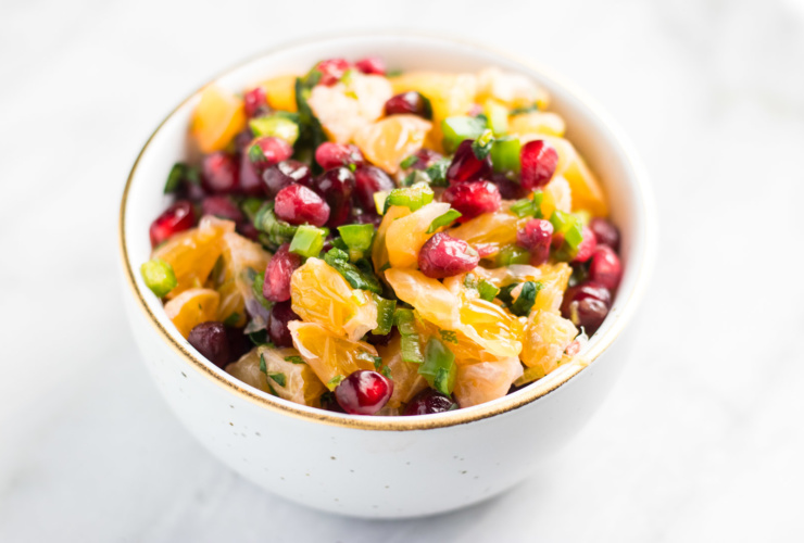 White bowl with a gold rim filled with low FODMAP Pomegranate Orange Salsa