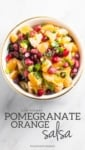 Low FODMAP Pomegranate Orange Salsa in a white bowl sitting on a white marble background with a gray text overlay of the recipe name.
