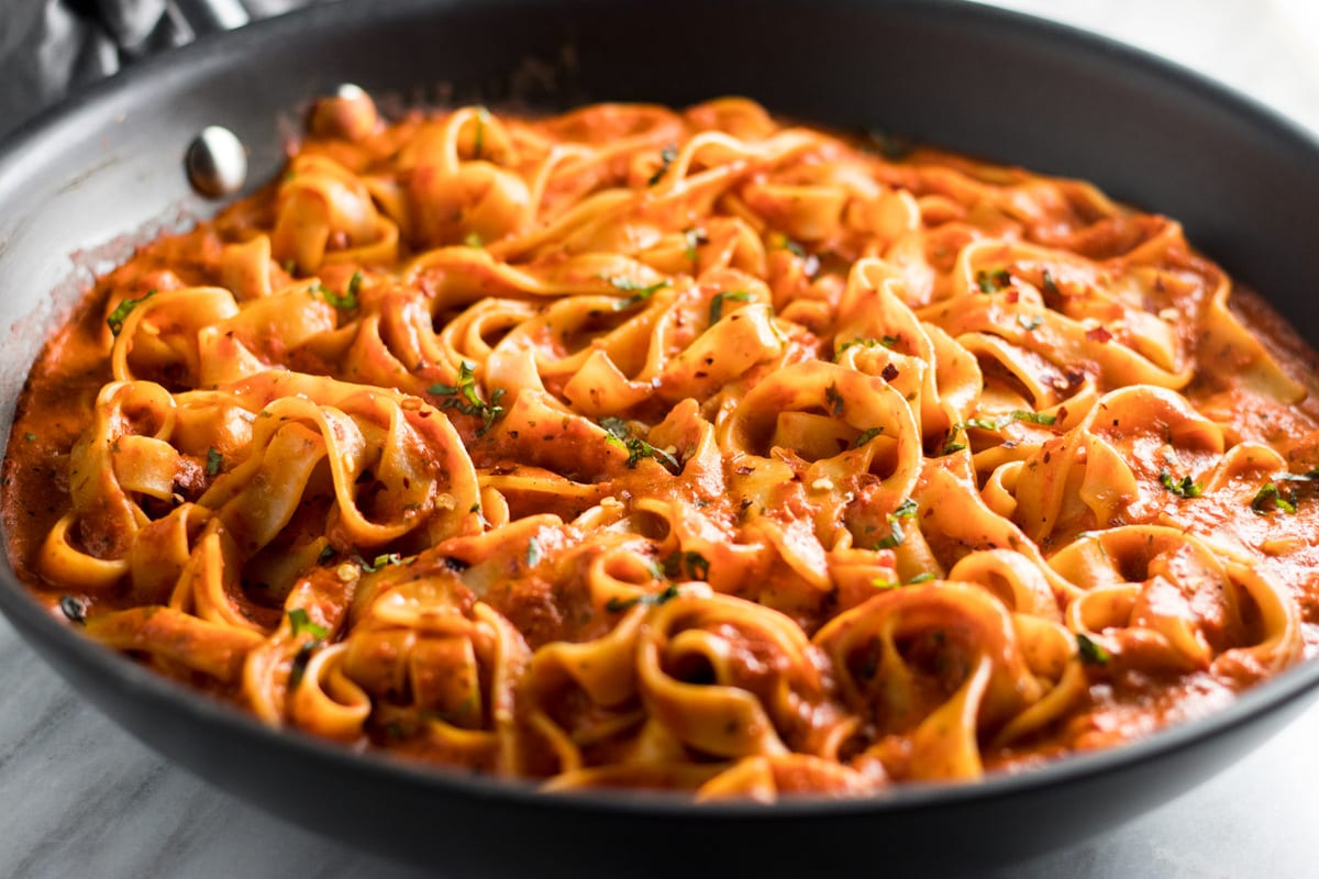 Horizontal close-up of Low FODMAP Roasted Red Pepper Pasta in a black skillet.
