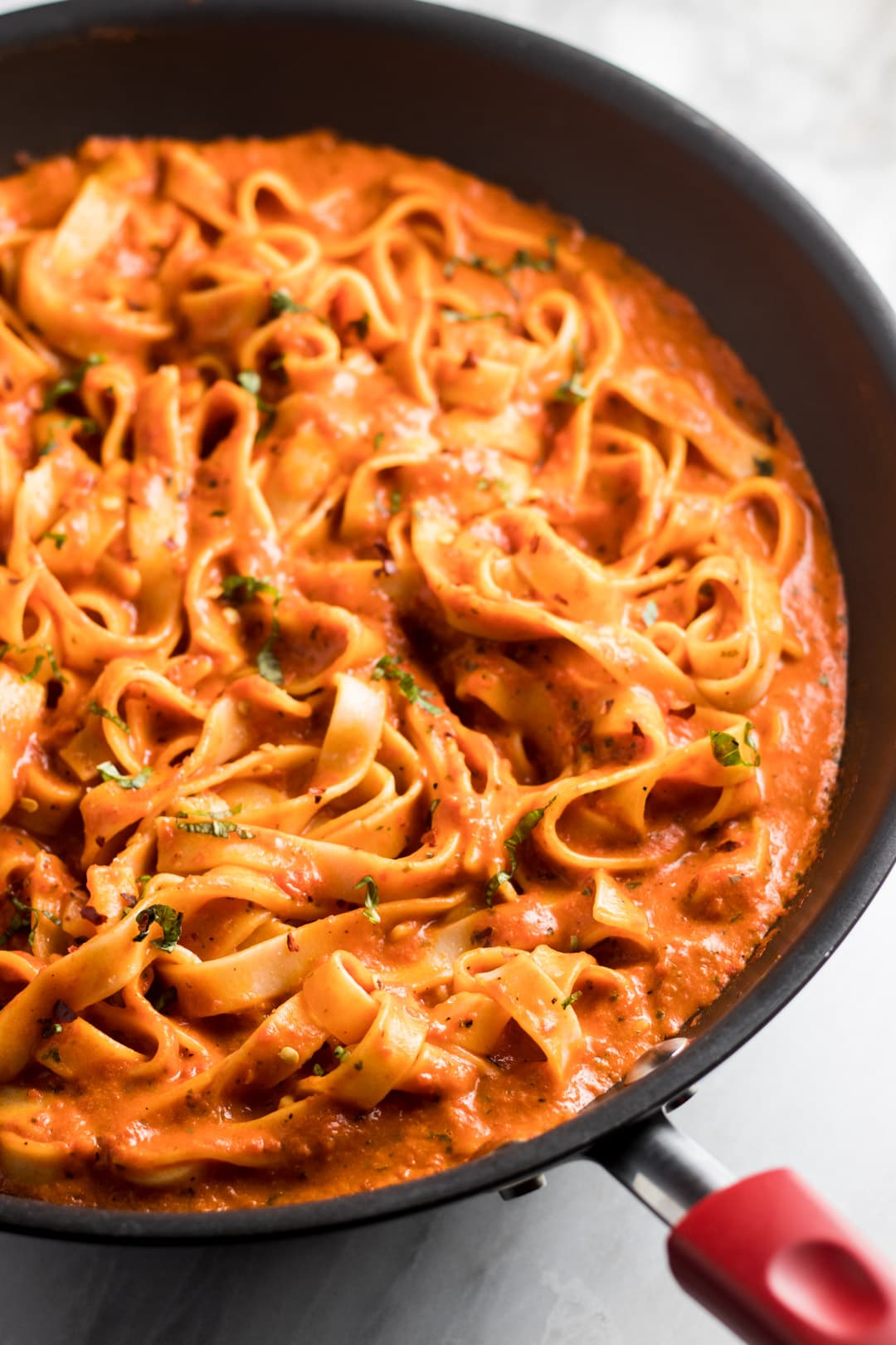 Fettuccine swimming in a roasted red pepper sauce and topped with finely sliced fresh basil.