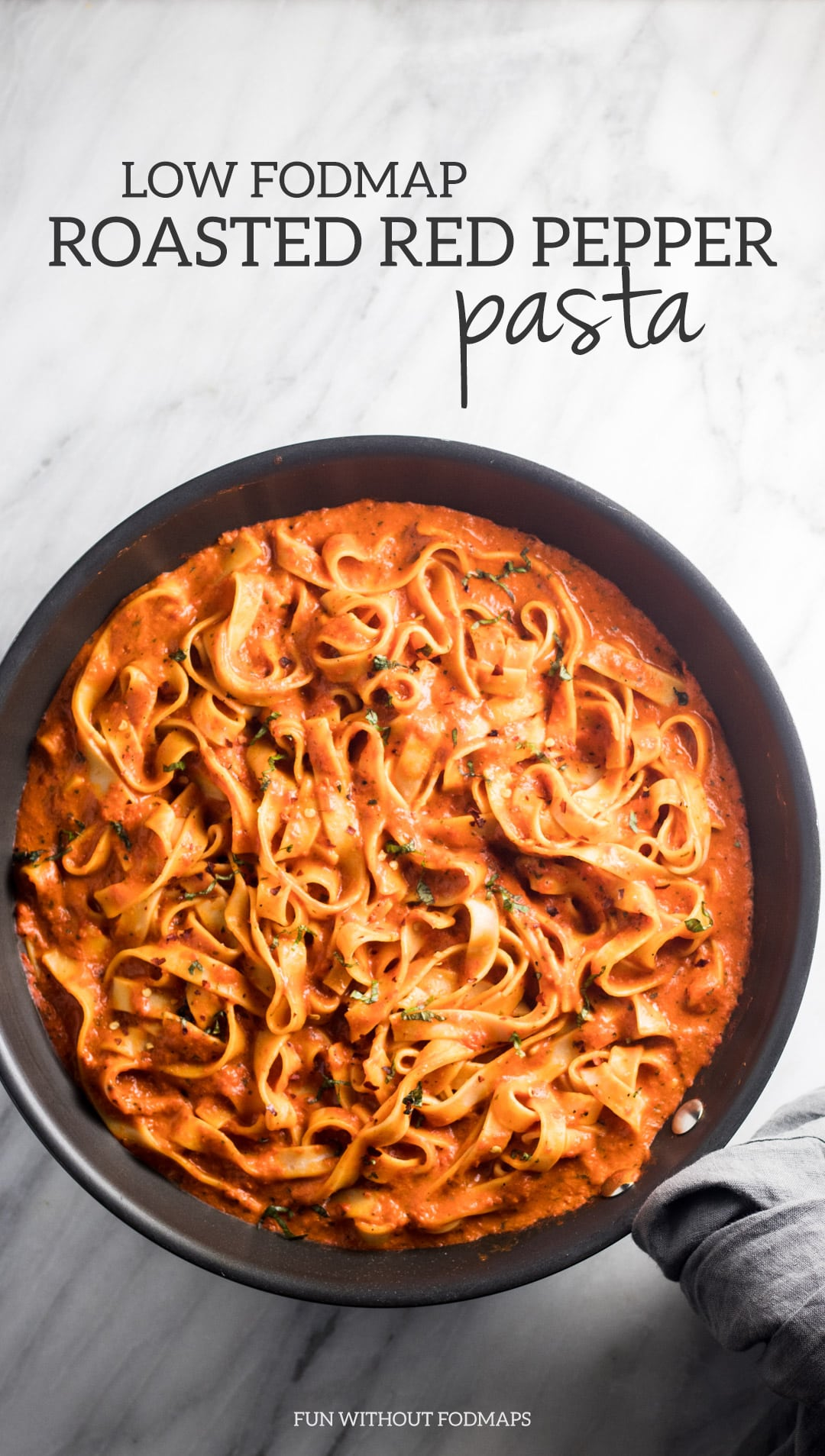 Looking down at a skillet filled with fettuccini tossed in a red pepper sauce. The skillet handle is wrapped in a gray linen napkin. Above the skillet a black text overlay reads Low FODMAP Roasted Red Pepper Pasta