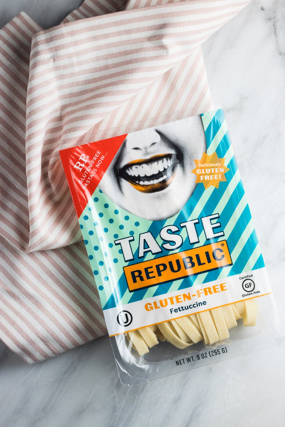 A package of Taste Republic Gluten Free Pasta on a light pink and white striped cloth napkin