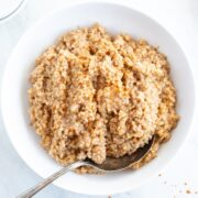 An overhead shot of a large white bowl filled with Instant Pot Low FODMAP Steel Cut Oats. There is an antique serving spoon grabbing a scoop.