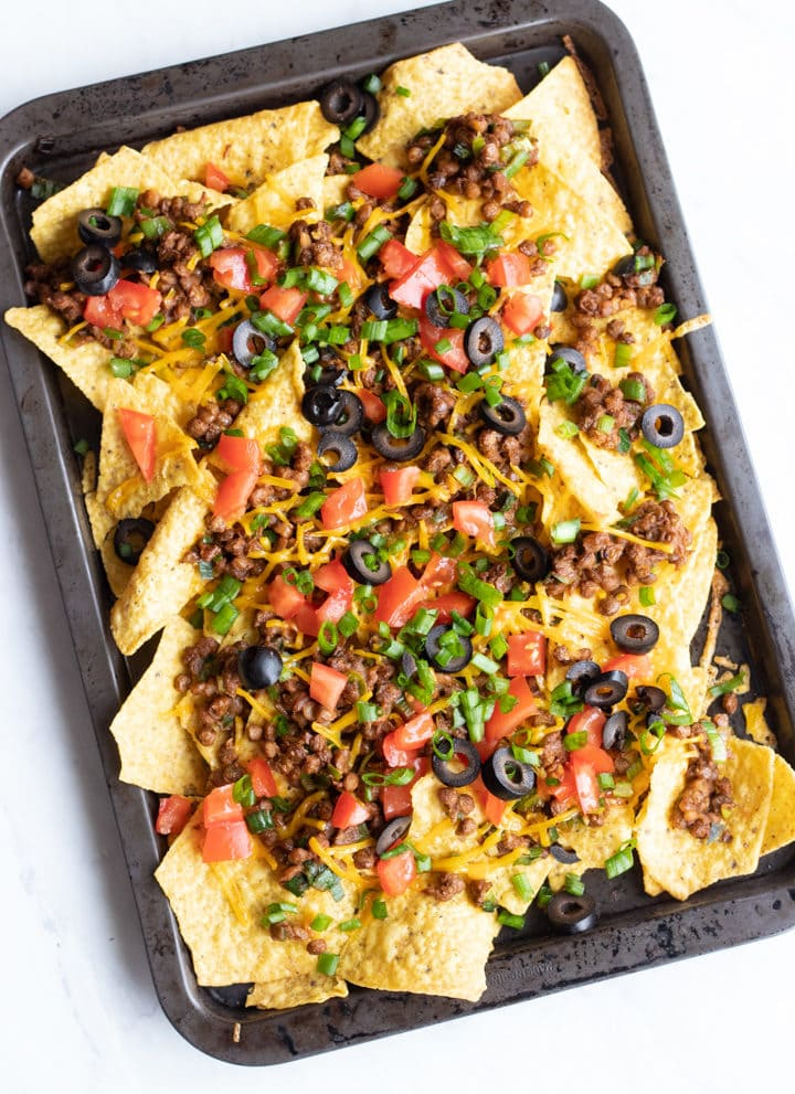 An overhead shot of a jelly roll pan filled with loaded low FODMPA lentil nachos.