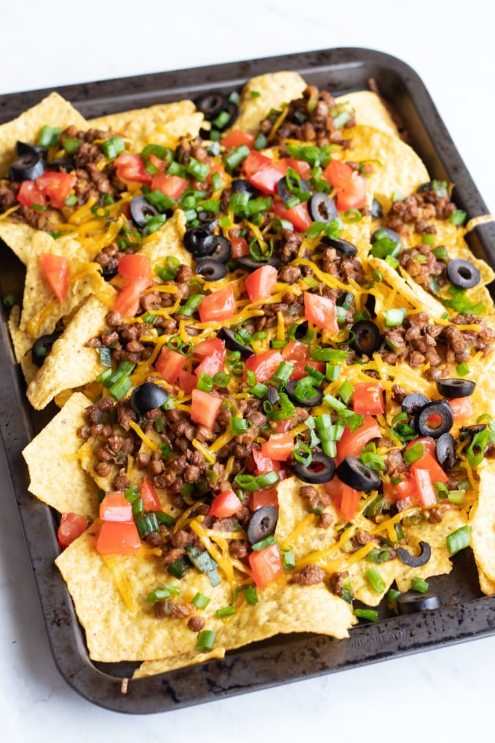 A pan filled with colorful and loaded low FODMAP lentil nachos