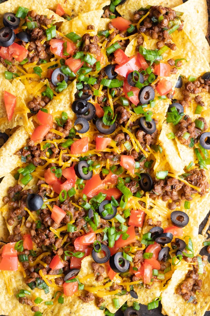 Close up of loaded low FODMAP lentil nachos topped with diced fresh tomatoes, black olives, and the sliced green tops of green onions.