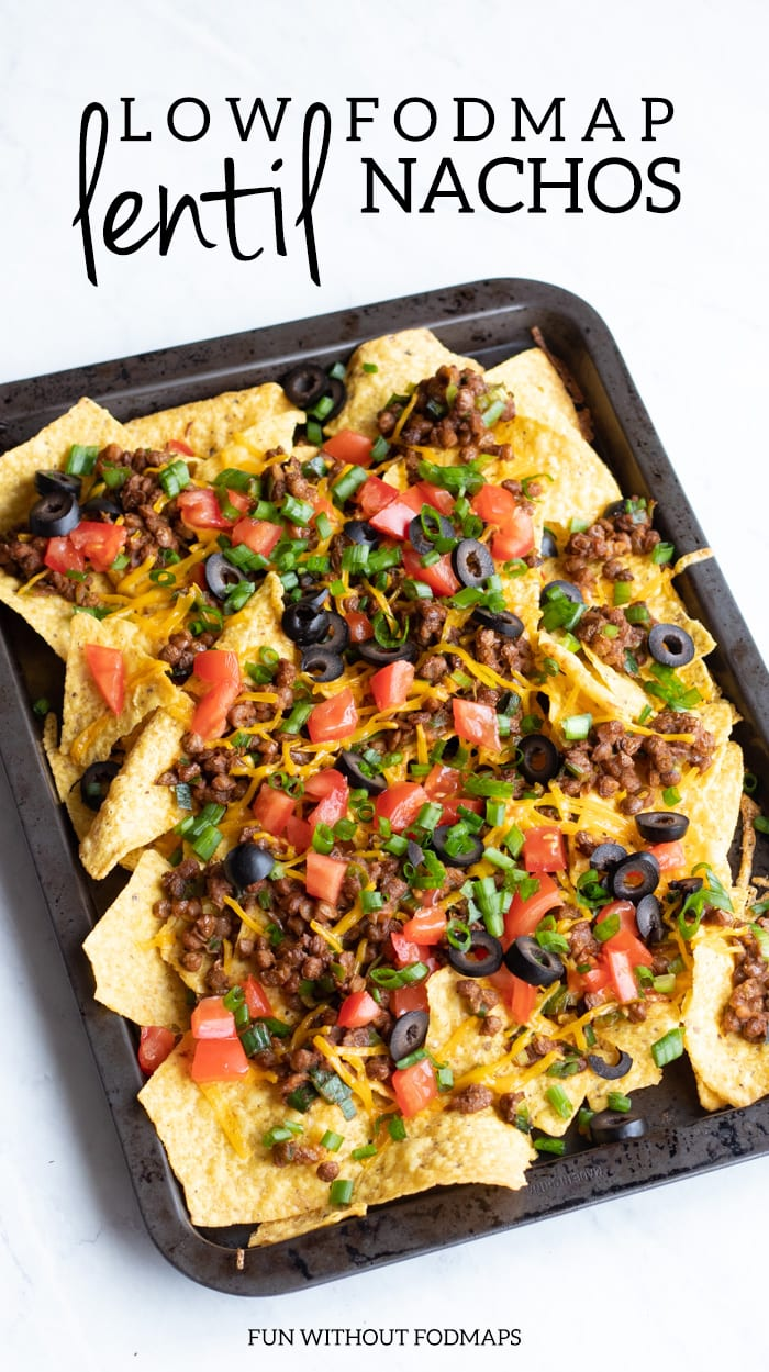 A close up of a pan filled with loaded low FODMAP lentil nachos. The pan is sitting on a white marble slab. Dark gray text reads low FODMAP lentil nachos and at the bottom it reads FUN WITHOUT FODMAPS.