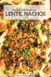 Close up of loaded low FODMAP lentil nachos topped with diced fresh tomatoes, black olives, and the sliced green tops of green onions. A white faded rectangle is centered at the top and filled with dark gray text that reads loaded low FODMAP lentil nachos.