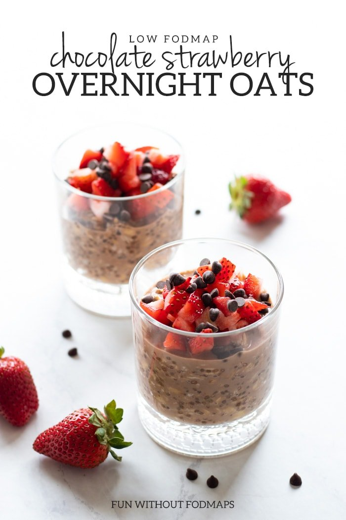 Two clear glasses filled with overnight oats and topped with diced strawberries and mini chocolate chips. There are strawberries and mini chocolate chips scattered around them on the white marble slab everything is sitting on. Centered dark gray text reads low FODMAP chocolate strawberry overnight oats at the top of the image.