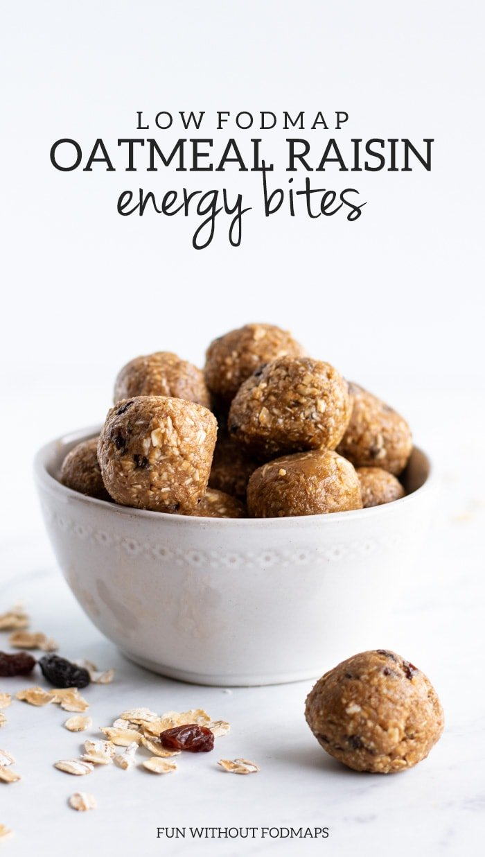 Low FODMAP Oatmeal Raisin Energy Bites fill a white bowl sitting on a white marble slab.