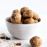 A small white bowl filled with golf ball sized low FODMAP oatmeal raisin energy bites. The bowl is sitting on a white marble slab. There is a bite in the foreground as well as a sprinkle of rolled oats with a couple of stray raisins.